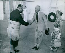 Wearing a mat tied around his middle, H.R.H. Prince Tungi (left), eldest son of Queen Salote and Premier of Tonga, greets Sir Kenneth and Lady Maddocks on their arrival in Nukualofa.