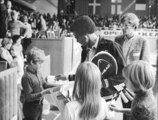 American tennis player Arthur Ashe writes autographs for some young fans during the Stockholm Open 1971