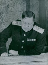 A photo of a Soviet military commander Fyodor Ivanovich Tolbukhin looking something on the table.