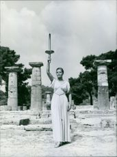 Woman standing and holding stand.