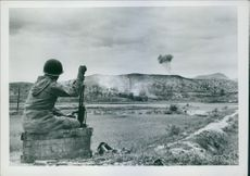 A photo shows a lone infantryman sets with his b.a.r., watching Napalm bombs hitting the enemy (background) along the Naktong River front. 1950