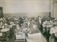 Children sitting and unwrapping their gifts. 1918