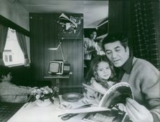Daniel Gelin reading magazine with his daughter, woman looking at them.  1966