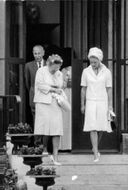 Queen Juliana climbing down the stairs along with a woman.