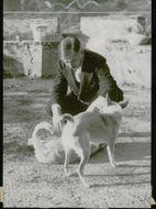 French politician Pierre Laval along with one of his dogs outside the castle he has as a residence. - 10 September 1944