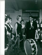 Sacha Distel and a woman admiring the band members. Photo taken June 7, 1960