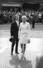 Princess Irene and Carlos Hugo with crowd standing on the side of the street looking at them.
