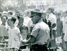 People gathered on road and a policeman standing.