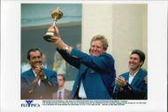 Golf player Colin Montgomerie holds up the trophy in the company of Seve Ballestaro and José María Olazábal after the win in the Ryder Cup 1997