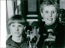 A joyful Mrs. Judith Dozier, with her daughter Cheryl, attending a press conference. 1982.