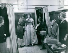 Princess Kira of Prussia wearing a gown, women fixing her gown, 1960.