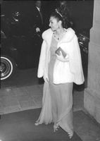 Farah Pahlavi standing and smiling while looking behind her back.