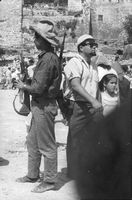 An armed man standing with people walking around, in Israel.