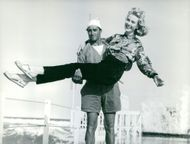 Emma Danieli smiles while being carried by the man in shorts, as they posed for the camera.