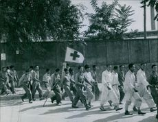 Group of men walking in line with a flag that has a cross in it. 1950