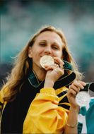 Ludmila Engquist proudly shows his gold medal for the 100 m win at the award ceremony during the Atlanta Olympic Games in 1996