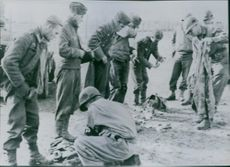 U.S. soldiers search German prisoners in Italy.