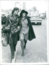 Sweet couple talking and smiling while walking down the street, 1971