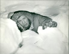 A man peeping through snow shelter.