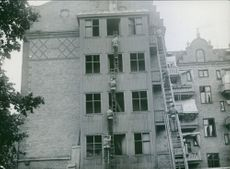 Policemen climbing over the building by ladder.