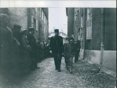 Policemen holding and taking away a woman and people looking in the street.