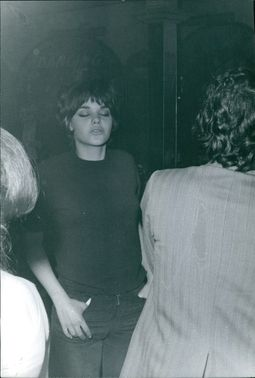 Vintage photo of Daris standing and with her hands on her pockets.