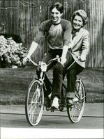 Nancy Reagan cycles tandem bike with his son Ronald Reagan Jr. at the White House