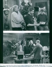 """Director Donald Petrie, Whoopi Goldberg, Eli Wallach and other staff and casts on the set of the comedy film, """"The Associate""""."""