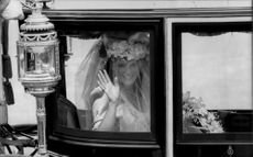 Sarah Ferguson waves to the spectators from the wagon on her wedding day