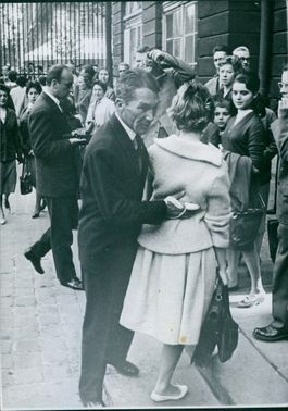 A man with a bondage on his finger holds the on her back as the people watch them walks,1959