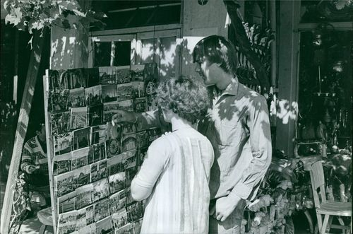 Man and woman looking at a display of postcards outside the store, 1966.