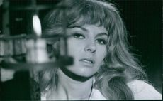 Close up photo of a French actress beautiful Michele Mercier front of it is a candle. 1967