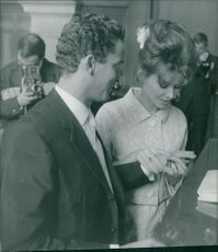 Irina Demich with man, looking at ring.