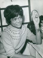 Eartha Kitt in jumper and a cigarette in his hand