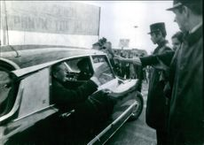 Nguyen Binh waving through the window of his car to the people standing in street.
