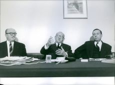 Three French politician Edgar Faure, Jacques Hersant and Guy Mollet are sitting together, Edgar Faure is discussing something with them