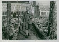 Stanley Baldwin walking in in the middle of a garden, while holding a cigarette.