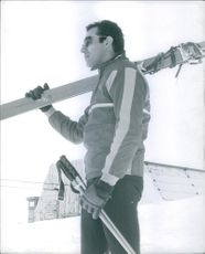 1970  A photo of Prince Consort of Denmark Prince Henrik standing in a snowy field, looking at something and smiling.