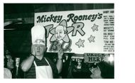 """Mickey Rooney points to a caricature of him on a sign and says, """"Is that me?"""""""