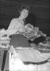 A Red Cross Youth girl in the process of packing the Christmas gifts for Greece.