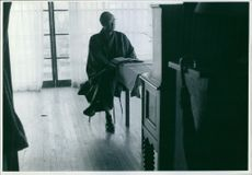 Ryotaro Azuma in a room sitting and holds a book on the table.