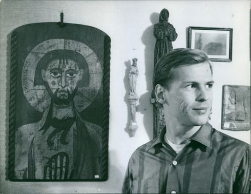 Photo of a man looking away from the portrait on the wall.