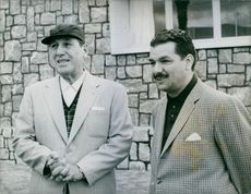 Juan Domingo Perón standing and talking with a man.