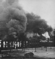 The smoke rises above an old building.