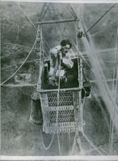 An illustration of a soldier riding a cable car to cross a high altitude mountain.