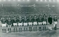 Yugoslav National Soccer team players standing in line in front of the spectators in the stadium.