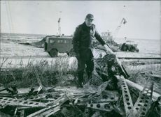 Soldiers standing beside the debris and looking at the camera and smiling.