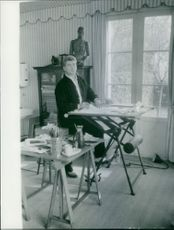 A photo of a French actor, writer, director and sculptor Jean-Alfred Villain-Marais doing some paper work sitting on a table looking for something in a room.