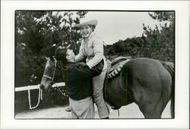US President Ronald Reagan helps his wife Nancy down from a horse at their ranch El Cielo