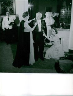 Two women helping André Maurois with his suit.